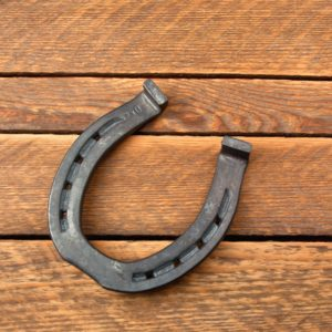 Iron horse shoe on wooden table