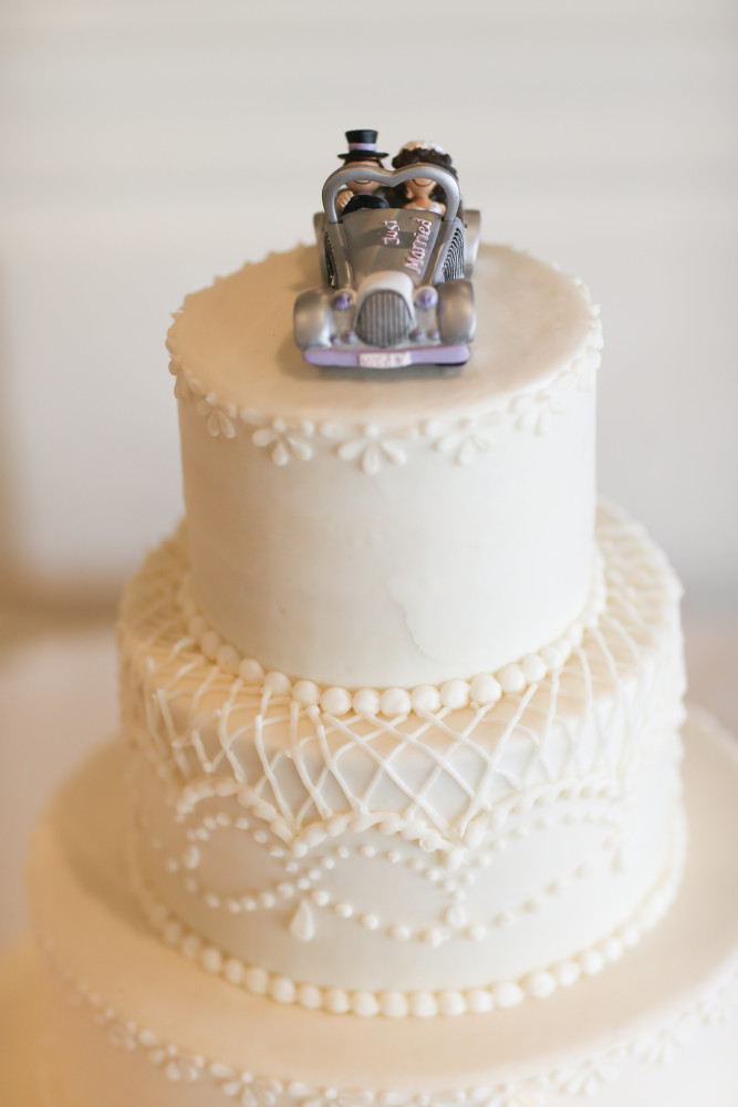 A classic tiered wedding cake with a custom bride and groom topper